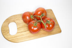 Four fresh on the vine red tomatoes on wood cutting board Stock Photos