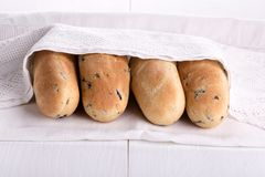 Four freshly baked mini baguette with olives and rosemary stock photos