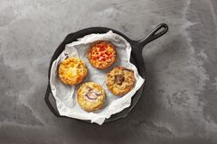 Four quiches in a pan. Four freshly baked quiche pies in a cast iron pan on a dark slate effect surface stock images