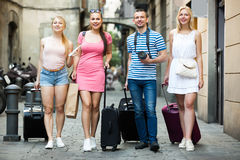 Four friendly traveling persons walking in city Royalty Free Stock Photography