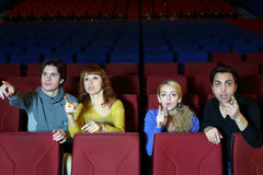 Four friends amaze and point finger at screen. Four young friends amaze and point finger at screen in cinema theater stock image