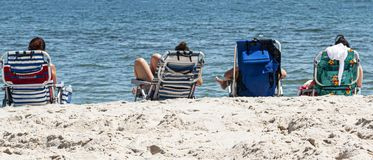 Four friends in beach chairs by the ocean. View from behind of four women relaxing in beach chairs overlooking the ocean at the beach royalty free stock images