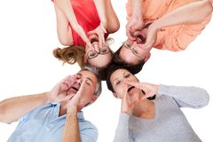 Four friends calling out. Conceptual image of four middle-aged friends calling out with their hands to their mouths and their heads together  on white Stock Photos