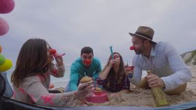 Young friends partying together on the beach on a winter day. Four friends celebrate birthday on the beach with red noses and colorful whistles stock video footage