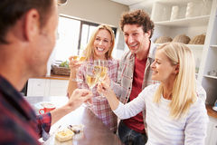 Four friends celebrating at home Royalty Free Stock Image