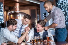 Four friends compete at the hands of drink beer and spend time t Royalty Free Stock Images