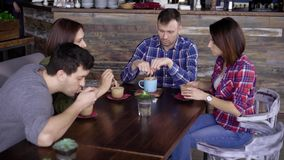 Four friends drinking coffee together. Group of two women and two men sitting in cafe and drinking coffee together stock footage