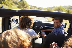 Four friends driving in an open top car, elevated view Stock Photos