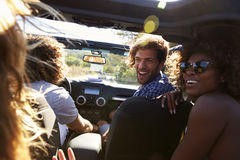 Four friends driving in an open top car, rear passenger POV Royalty Free Stock Images