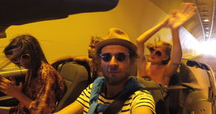 Four friends driving through tunnel in convertible car stock video footage