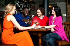 Four friends enjoying dinner at a restaurant Royalty Free Stock Photos