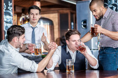 Four friends fooling around drinking beer and spend time togethe Stock Image
