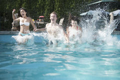 Four friends holding hands and jumping into a pool, mid-air Stock Image