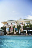 Four friends holding hands and jumping into a pool, mid-air Royalty Free Stock Photos