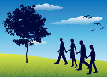 Four friends holding for hands and walking on field. Near tree, blue sky Royalty Free Stock Photo