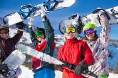 Four friends holding snowboards and skies. Four happy friends standing together and holding snowboards and skies looking straight royalty free stock photography