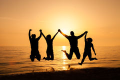 Four friends jumping on the beach. At sunset Royalty Free Stock Photos