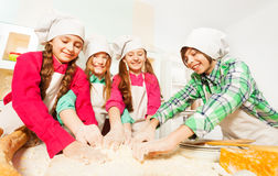 Four friends kneading bakery dough at the kitchen Royalty Free Stock Image