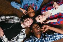 Four friends listen music together, lay on floor. Friends Company Music Together Happy Friendship International Freedom People Unity Race Equality Concept Royalty Free Stock Photos