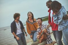 Group of happy friends are singing on seaside. Four friends listening their favorite songs while one of them playing acoustic guitar royalty free stock photo