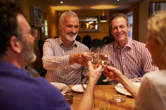 Four friends making a toast during a meal at a restaurant Stock Photo