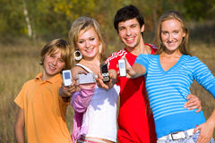 Four friends with mobile phones Royalty Free Stock Photos
