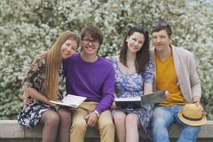 Four friends in the Park with books Stock Photo
