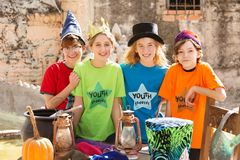 Four friends pose by pumpkin. Four friends stand together beside a pumpkin and cauldron to pose for camera Stock Photos