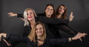 Four friends posing in a studio with a black background royalty free stock photo
