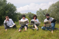 Four friends read newspapers Stock Photos