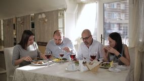 Four friends in the restaurant, eat meat and drink red wine in the glass. stock footage