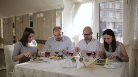 Four friends in the restaurant, eat meat and drink red wine in the glass. stock video