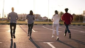 Four friends are running by empty parking zone outdoors - fun happiness, young men and women are running in the evening stock video footage