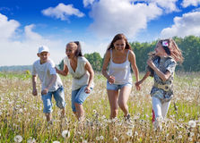 Four friends running at meadow Stock Images
