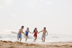 Four friends running out of the water on a sandy beach Stock Image