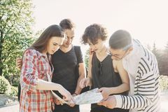 Four friends searching the location on city map. Traveling, sightseeing, group travel, city tour, student exchange program, togetherness. Four young friends Royalty Free Stock Photos