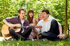 Four friends singing by guitar Royalty Free Stock Photography