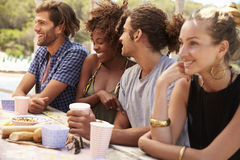 Four friends sit in a row at a table by the sea, close up Royalty Free Stock Photography