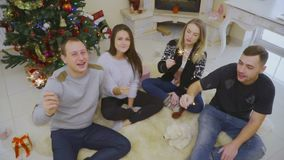 Four friends sits on floor with sparklers celebrating Christmas. Two girls and two boys sit on the fluffy carpet and light sparklers. Christmas tree is lighting stock video