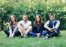 Four friends sitting cross-legged on lawn and looking at camera. Young stylish women and men in casual clothes resting on nature. Beautiful male and female Royalty Free Stock Photos