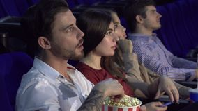 Four friends are sitting in the cinema hall and watching the movie. Four friends are sitting in the same row at the cinema. The guy eats popcorn. Near seats his stock video