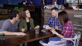 Four friends sitting at the table in cafe enjoying their meal and talking to each other. Two couples chatting while. Four friends are sitting at the table in stock video footage