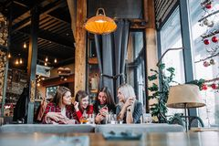 Four friends sitting by the table in cafe and making selfie on smartphone. Four beautiful young women doing selfie in a cafe, best friends girls together having Royalty Free Stock Images