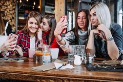 Four friends sitting by the table in cafe and making selfie on smartphone. Four beautiful young women doing selfie in a cafe, best friends girls together having Stock Photos