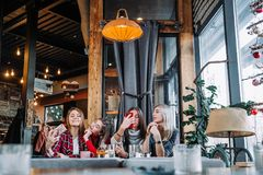 Four friends sitting by the table in cafe and making selfie on smartphone. Four beautiful young women doing selfie in a cafe, best friends girls together having Royalty Free Stock Photos