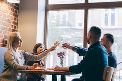 Four friends sitting together with glasses of champagne. Four friends sitting together, holding glasses of champagne, toasting. Quality time with friends Royalty Free Stock Photo