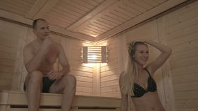 Four friends sitting on the wooden benches and soaring in the sauna. Two young beautiful girls in pink and black swimsuit and two attractive men sitting on the stock video footage