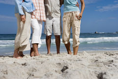 Four friends standing on sandy beach, low section, surface level Royalty Free Stock Photography