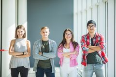 Four friends standing with crossed hands and smiling indoors. Fours students in university. Four friends standing and smiling. Four friends standing. Fours Stock Images