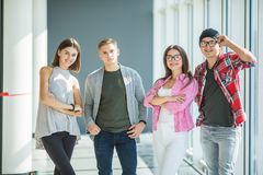 Four friends standing and smiling indoors. Fours students in university. Four friends standing and smiling. Four friends standing. Fours students in university Stock Images